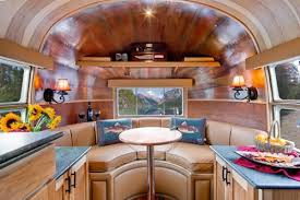 Airstream with couches at one end with a curve.
