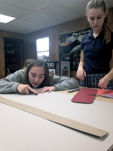 Hard at work on the model using the X-Acto Knife, while Ally discusses solar panel calculations.