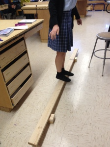 """Classmate Shahar stands on a 2""""x4"""" member to calculate beam deflection."""