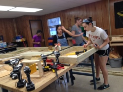 Shahar works on the back wall and makes sure that each 2x4 is square.